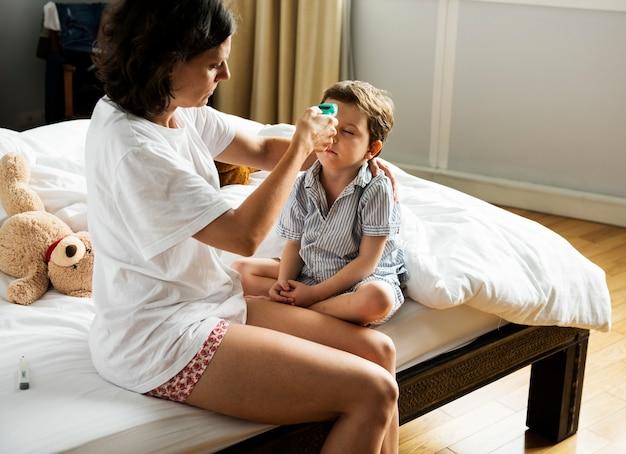 Garçon Assis Sur Le Lit Et Sa Mère Vérifiant La Température Photo Premium