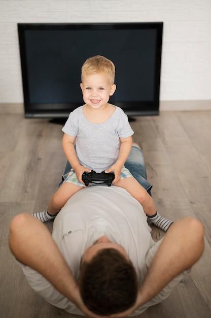 Garçon Assis Sur Le Père Et Jouant Avec Une Manette De Jeu Photo gratuit