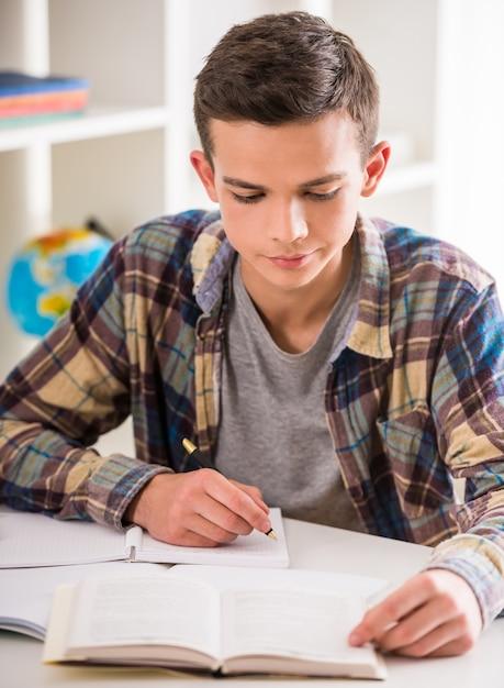 Garçon assis à la table et fait ses devoirs à la maison. Photo Premium