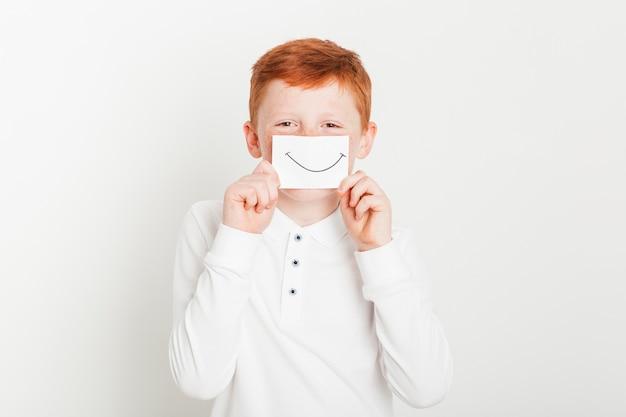 Garçon au gingembre avec carte de bouche souriante Photo gratuit