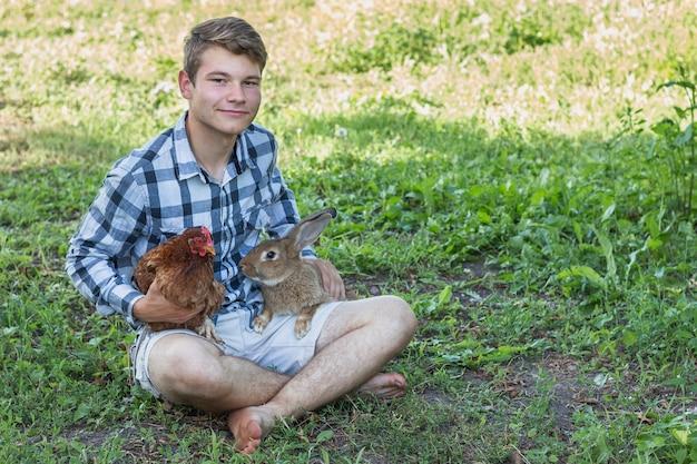Garçon aux jambes croisées tenant des lapins et du poulet Photo gratuit