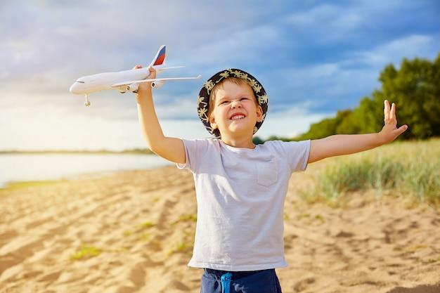 Garçon avec un avion dans ses mains sur la plage Photo Premium