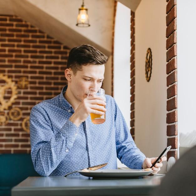 Garçon ayant une bière au restaurant Photo gratuit