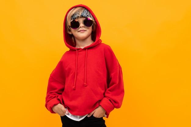 Garçon Blond Avec Un Bandana Sur La Tête Dans Un Sweat à Capuche Rouge Et Des Lunettes Posant Sur Un Fond Orange Photo Premium