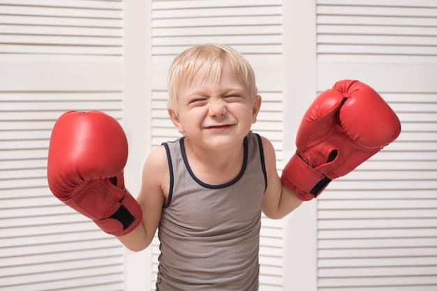 Garçon Blond Drôle Dans Des Gants De Boxe Rouges. Concept Sportif Photo Premium