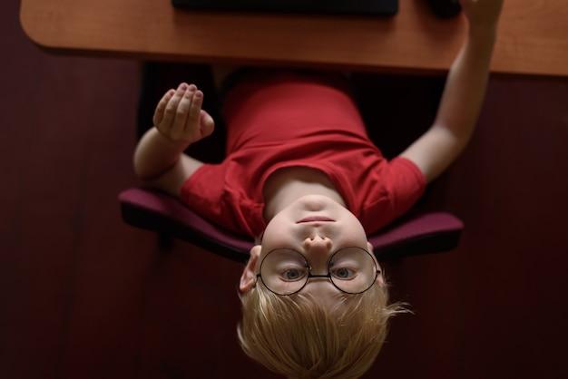 Garçon Blond Drôle Dans Des Verres Se Reposant Sur Un Ordinateur Portable. Internet Et Enfant D'âge Préscolaire. Photo Premium