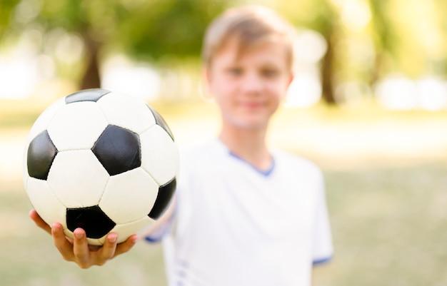 Garçon Blond Flou Tenant Un Ballon De Football Photo gratuit