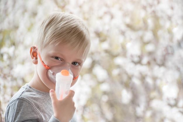 Garçon blond en inhalateur de masque de respiration sur les arbres en fleurs. Photo Premium