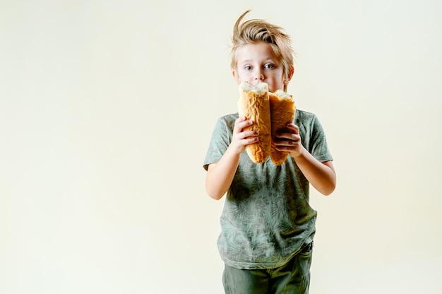 Un garçon blond mange une baguette parfumée, des pâtisseries fraîches. savoureux petit déjeuner Photo Premium