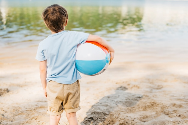 Garçon avec boule de vent en regardant l'eau Photo gratuit