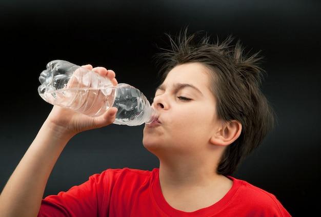 Garçon buvant dans le noir Photo Premium