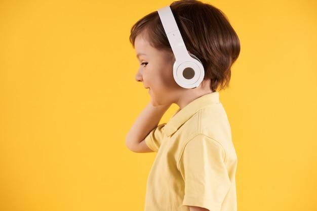 Garçon avec un casque écoute de la musique vue de côté. Photo Premium