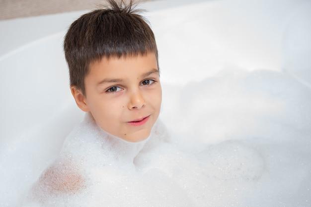 Garçon caucasien souriant prend un bain avec de la mousse. enfance, prendre un bain, thème hygiène. Photo Premium