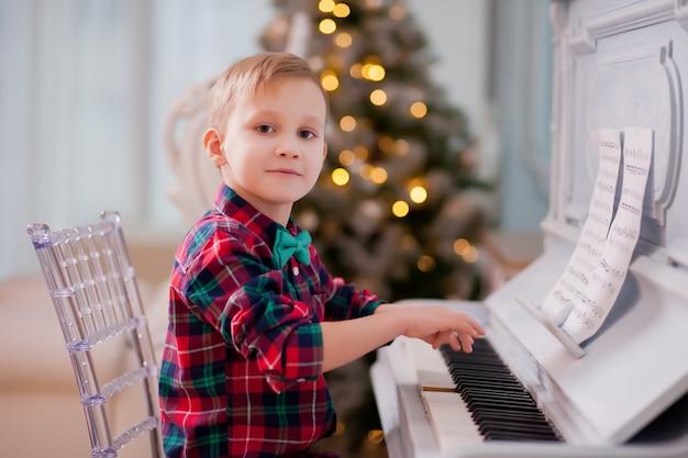 Garçon En Chemise à Carreaux Et Cravate Papillon Jouant Du Piano. Concept De Noël. Photo Premium