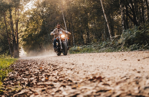 Un garçon conduire une moto sur la route de pierre Photo Premium