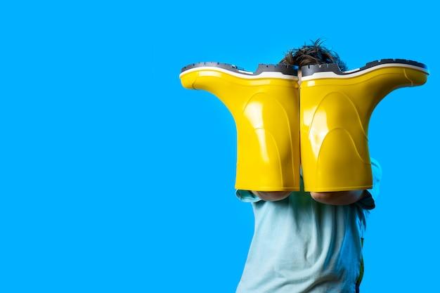 Un garçon a couvert son visage avec des bottes en caoutchouc jaune Photo Premium