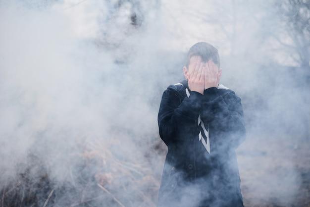 Le Garçon A Couvert Son Visage Avec Ses Mains Dans Une épaisse Fumée. Photo Premium