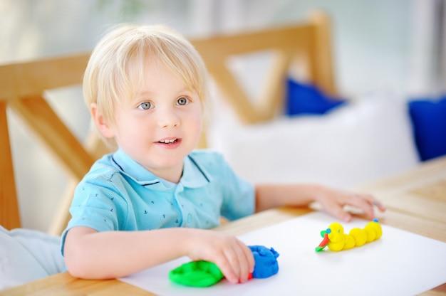 Garçon créatif jouant avec de la pâte à modeler colorée à la maternelle Photo Premium