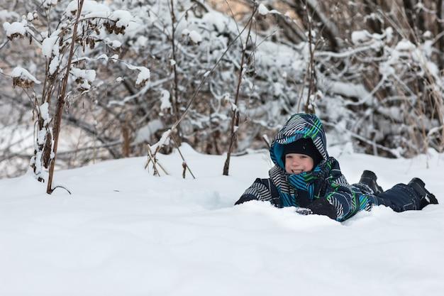 Le garçon dans la forêt d'hiver. Photo Premium