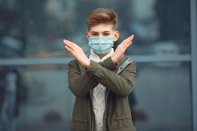 Un garçon dans un masque jetable croisant les bras Photo gratuit