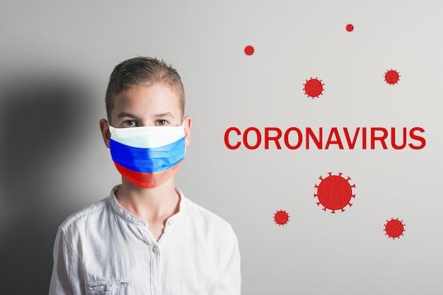 Garçon Dans Un Masque Médical Avec Le Drapeau De La Russie Sur Son Visage Sur Fond Clair. Photo Premium