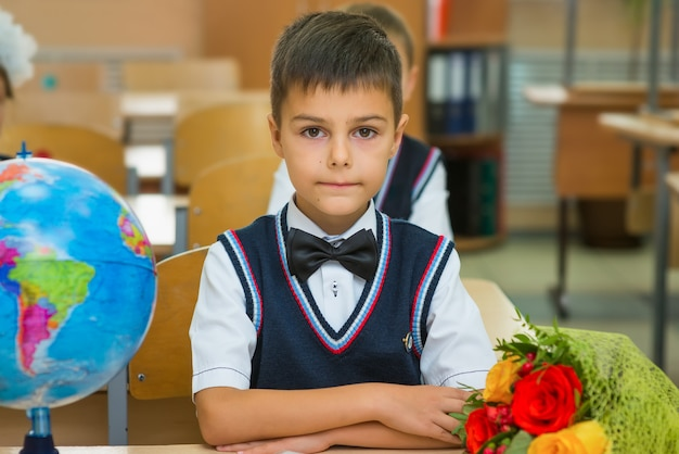 Garçon dans la salle de classe au bureau avec globe et bouquet de fleurs. Photo Premium