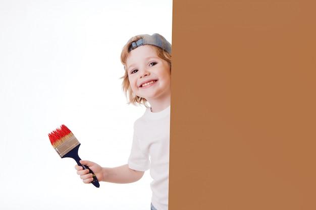 Garçon dans un t-shirt blanc avec un pinceau dans les mains, peint au mur, écrit. Photo Premium