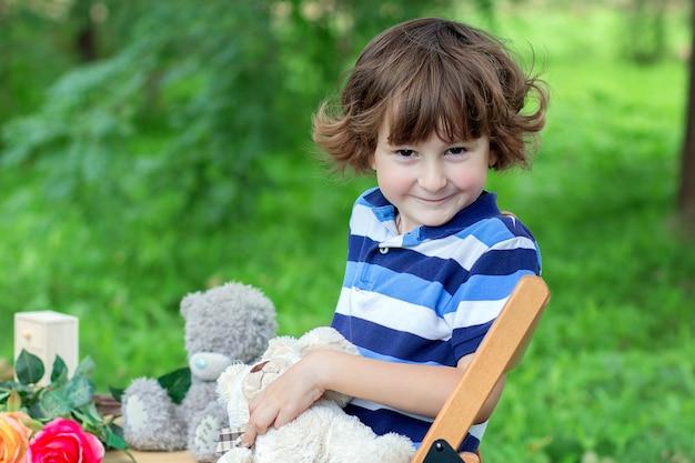 Le garçon dans un t-shirt bleu rayé est assis sur un tabouret à l'extérieur parmi les verts Photo Premium