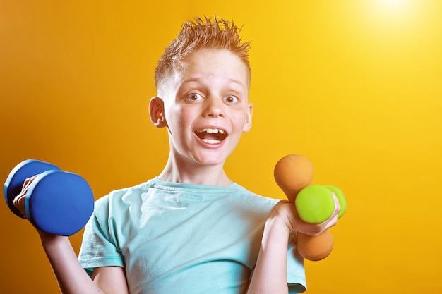 Un garçon dans un t-shirt lumineux avec des haltères sur un jaune Photo Premium
