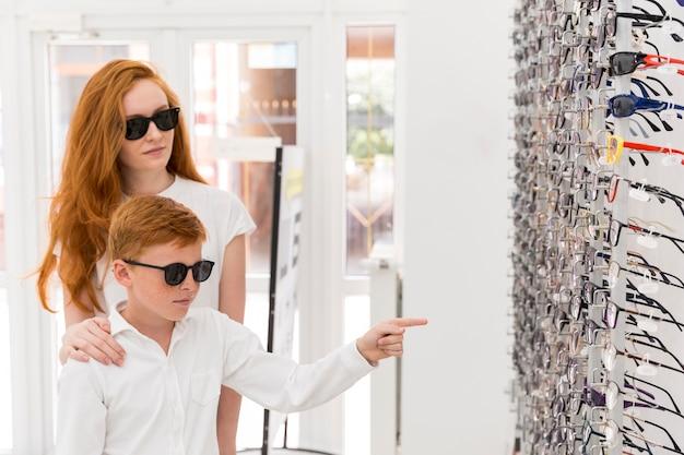 Garçon debout avec sa soeur dans le magasin d'optique et pointant au porte-lunettes Photo gratuit