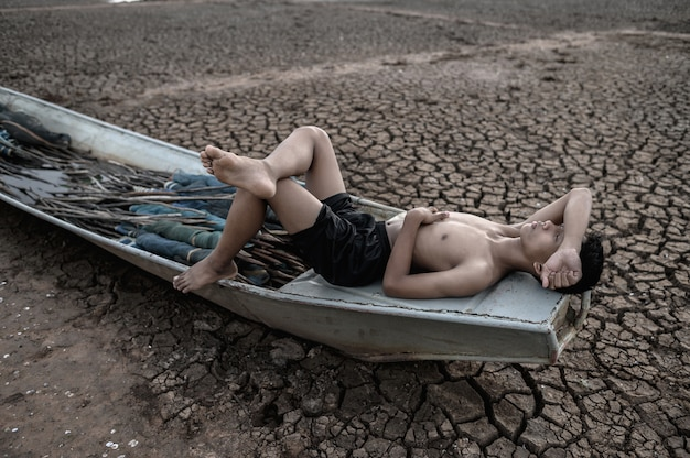 Le garçon a dormi sur un bateau de pêche et a posé ses mains sur le front sec sur le sol, réchauffement climatique Photo gratuit