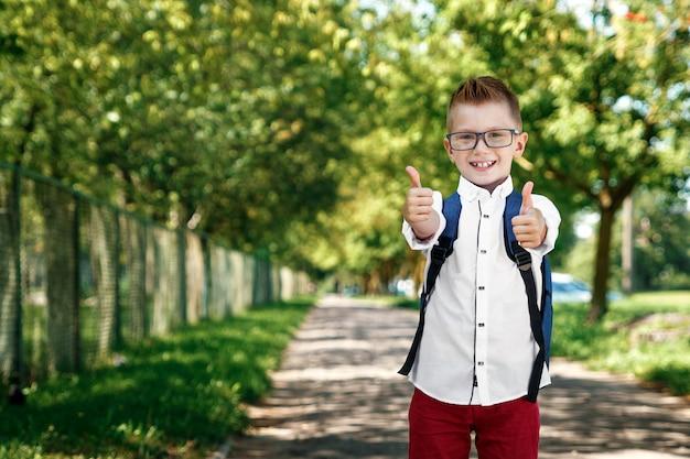 Un garçon d'une école primaire avec un sac à dos dans la rue Photo Premium