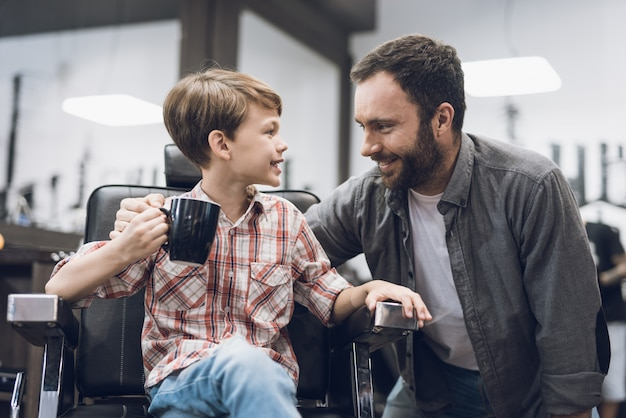 Le garçon écoute un homme adulte assis dans un salon de coiffure. Photo Premium