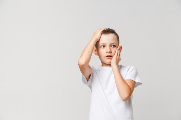 Garçon Effrayé En T-shirt Blanc Avec Les Deux Mains Sur La Tête Sur Fond Gris Photo Premium