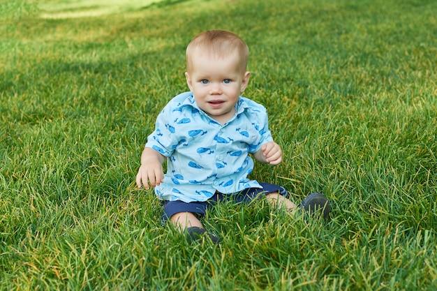 Garçon enfant sur l'herbe dans le parc Photo Premium