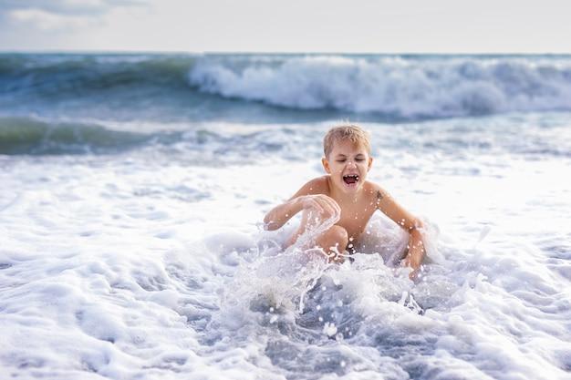 Garçon enfant jouant dans les vagues sur la plage au coucher du soleil de l'été Photo Premium