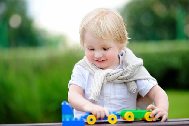 Garçon enfant jouant avec train jouet en plein air à la chaude journée d'été. jouets pour petits enfants Photo Premium