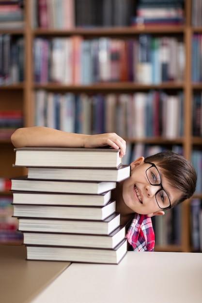Garçon Espiègle Se Cachant Derrière Une Pile De Livres Photo gratuit