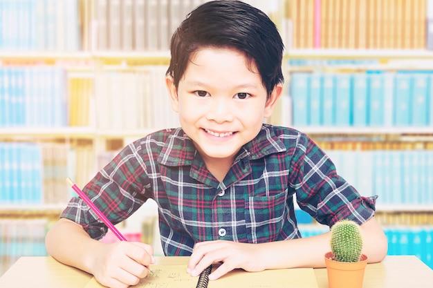 Un garçon est heureux de faire ses devoirs dans une bibliothèque Photo gratuit