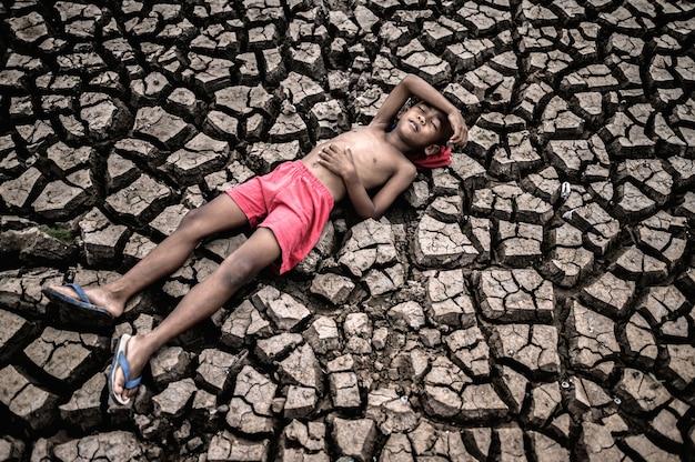 Le garçon était étendu à plat, posant ses mains sur le ventre et le front sur un sol sec. Photo gratuit