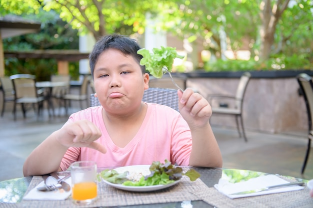 Garçon avec expression de dégoût contre les légumes Photo Premium