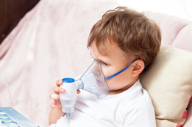 Garçon faisant l'inhalation avec un nébuliseur à la maison et regardant un livre Photo Premium