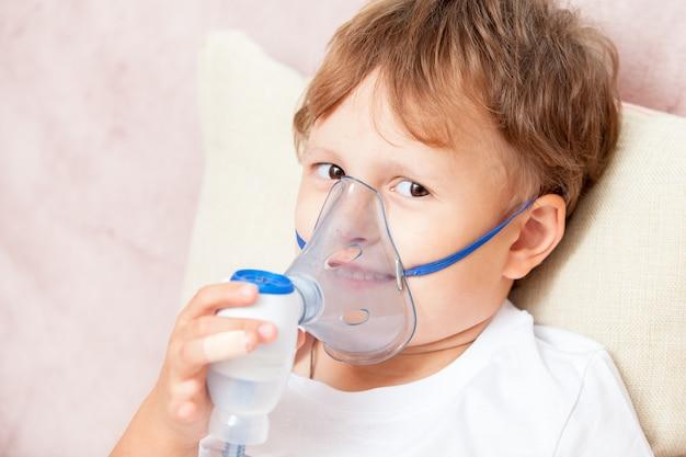 Garçon faisant l'inhalation avec un nébuliseur à la maison Photo Premium