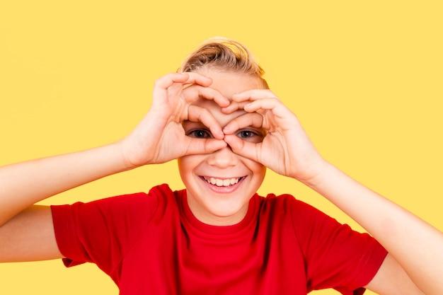 Garçon faisant des jumelles avec les mains sur ses yeux Photo gratuit