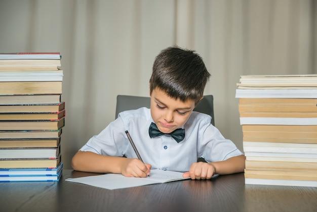 Un garçon fait ses devoirs. education, retour au concept d'école. Photo Premium