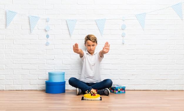 Garçon fête son anniversaire avec un gâteau faisant un geste d'arrêt avec sa main Photo Premium