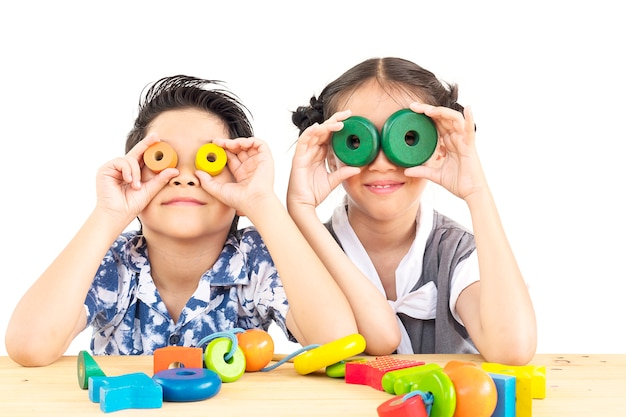 Un garçon et une fille asiatiques jouent avec joie sur un jouet coloré Photo gratuit