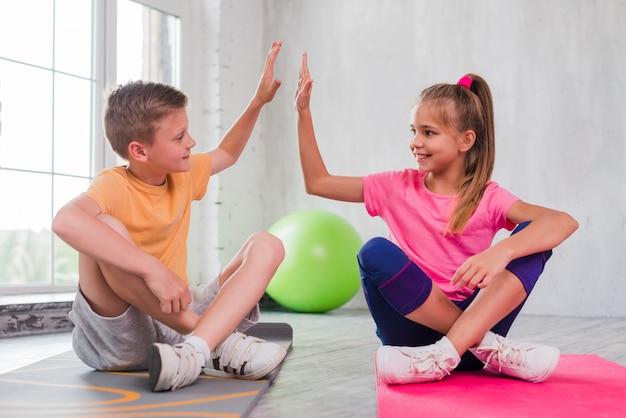 Garçon Et Fille Assis Sur Un Tapis D'exercice Photo gratuit