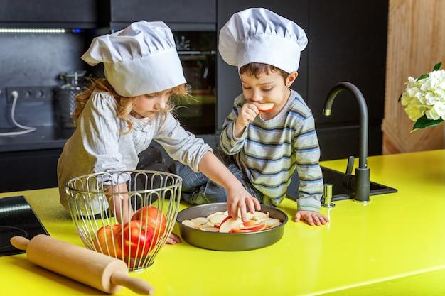 Garçon, fille, enfants, à, à, chapeau chef, préparer, cuire, tarte maison, à, pomme, dans, cuisine Photo Premium