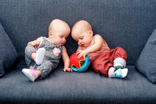 Un garçon et une fille avec un jouet jusqu'à un an sur le canapé. le concept de jumeaux dans la famille. Photo Premium